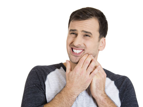 A man suffering from jaw pain after eating.