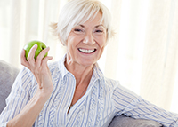 Older women about to eat an apple after learning to eat again with dentures from her Oral Surgeon in Glendale, AZ at Arrowhead Oral and Maxillofacial Surgery.