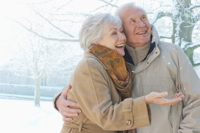 Older couple smiling in the winter after talking about dental implants for tooth loss with their Oral Surgeon in Glendale, AZ at Arrowhead Oral and Maxillofacial Surgery.